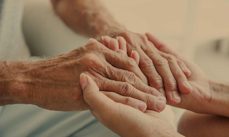 Ung och äldre person håller varandras händer